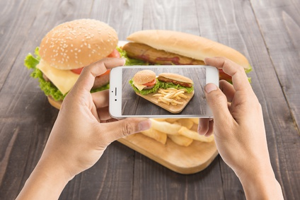 Friends using smartphones to take photos of hot dog and hamburger.